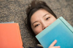 Student laying on carpet with books. Fun young student laying on carpet with a book covering mouth next to a stack of books Stock Image