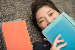 Student laying on carpet with books. Fun young student laying on carpet with a book covering mouth next to a stack of books Stock Photo