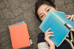 Student laying on carpet with books. Fun young student laying on carpet with a book covering mouth next to a stack of books Royalty Free Stock Photography