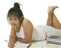 Student laying down doing homework Royalty Free Stock Photo