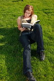 Student Laying On The Grass. A female student laying on campus lawn studying her text book Stock Images