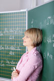 Student leaning against the blackboard Royalty Free Stock Photo