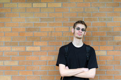 Student leaning against brick wall. A healthy tall white male Caucasian student stands in front of a brick wall with his arms crossed with confidence. Background Stock Image