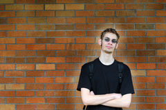 Student leaning against brick wall. A healthy tall white male Caucasian student stands in front of a brick wall with his arms crossed with confidence. Background Royalty Free Stock Images