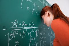 Student leaning head on blackboard in classroom Royalty Free Stock Photo