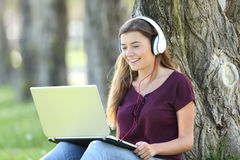 Student learning audio guides on line. Single student alone learning audio guides on line with headphones and a laptop in a park Royalty Free Stock Photo