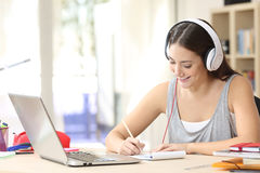 Student learning with headphones taking notes. Portrait of a student learning on line with headphones and laptop taking notes in a notebook sitting at her desk Stock Images