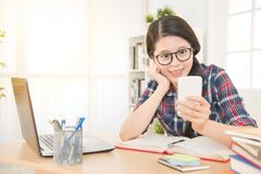 Student learning with laptop and texting. Beautiful relaxed student learning with laptop and texting in a mobile phone in a desk at home. mixed race asian Royalty Free Stock Images