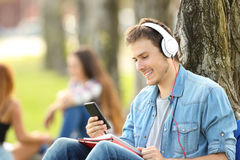 Student learning listening audio tutorials in a park. Sitting on the grass in a park Stock Photo