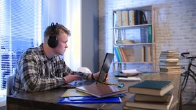 Student learning online with headphones and laptop. Concentrated student with headphones typing text on computer sitting at his desk at home. Handsome hipster