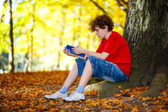 Student learning outdoor. Boy reading book in park Stock Photography