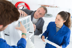 Student learns air conditioning repair from experienced instructor Stock Photo