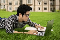 Student learns with laptop at park. Male student studying with laptop and book while lying down on the grass at school yard Royalty Free Stock Image