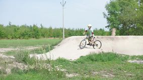 Schoolboy rides through the hills. A student learns to ride a bicycle on the hills stock video