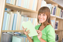 Student in library - cheerful woman choose book Royalty Free Stock Photos