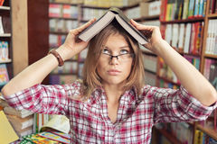 Student in library. Cute female student in high school or university library getting knowledge from the book. Funny blond Caucasian girl in eyeglasses looking up royalty free stock photo