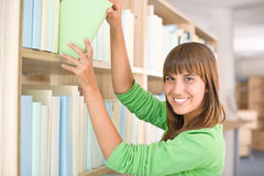 Student in library - happy woman choose book Royalty Free Stock Images