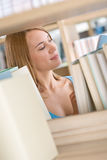 Student in library - happy woman study from book Stock Photos