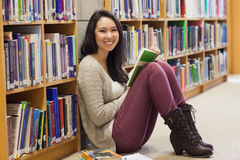 Student in a library leaning against a shelf Stock Image