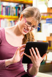 Student in library learning with tablet computer Stock Photo