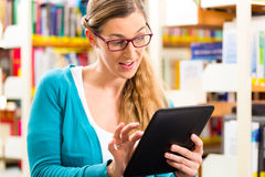 Student in library learning with tablet computer Royalty Free Stock Photos