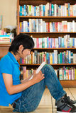 Student in library reading book Stock Photography