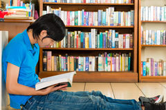 Student in library reading book. Student - Young man sits in library on the floor learning reading a book Royalty Free Stock Photo