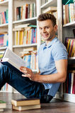 Student in library. Side view of handsome young man holding a book and smiling at camera while sitting on the floor and leaning at the library bookshelf Royalty Free Stock Photos