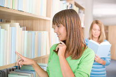 Student in library - two woman choose book Royalty Free Stock Photos