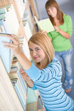 Student in library - two woman choose book Stock Image