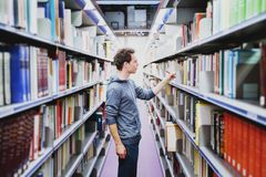 Student in the library of university. Young caucasian man taking book from bookshelf, education concept stock photography