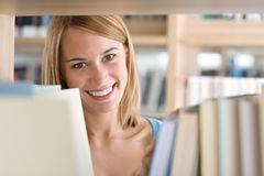 Student in library - woman look through bookshelf Royalty Free Stock Images