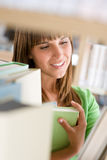 Student in library - woman stand by bookshelf Stock Image