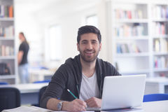 Student in a library working on a tablet. Student study in a library on a tablet. Hard worker and persistence concept royalty free stock photo