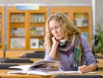 Student liest das Buch in der Bibliothek Stockfotografie