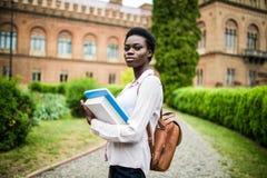 Student Life Ung gladlynt afrikansk högskolaflicka utomhus på modern universitetsområde arkivbilder
