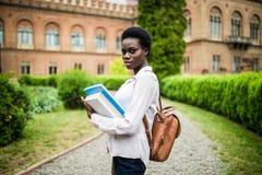 Student Life Ung gladlynt afrikansk högskolaflicka utomhus på modern universitetsområde arkivbild