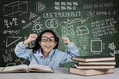 Student lifting hands with books and doodle in classroom Stock Photos