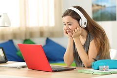 Student listening media content on line in her room Stock Images