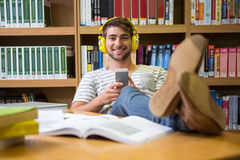 Student listening music in the library with smartphone Royalty Free Stock Photography