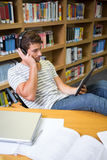 Student listening music in the library with tablet Royalty Free Stock Photos