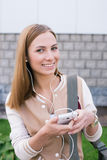 Student listening phone by headphones and smiling at camera. Student listening her phone by headphones and smiling at camera stock photos