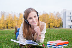 Student listening to headphones and holding opened book. Student listening to headphones, propping head by one hand and holding opened book by other hand stock image