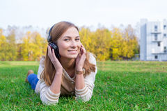 Student listening to headphones. Student laying on green grass and listening to headphones stock photo