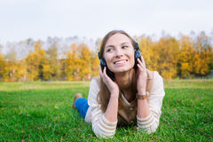 Student listening to headphones and looking towards. Student laying on green grass, listening to headphones and looking towards stock image