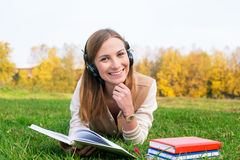 Student listening to headphones and reading book. Student lying on green grass, listening to headphones and reading book royalty free stock photos