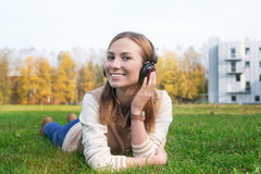 Student listening to headphones and touching earphone by hand. Student listening to headphones and touching one earphone by left hand on the sunset stock photography
