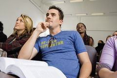 Student Listening To Lecture. Low angle view of student listening to lecture with friends in back Stock Photo