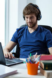 Student listening to the music. Smiling student listening to his favorite music on his headphones Royalty Free Stock Image