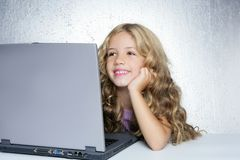 Student little school girl on laptop compute. Student little school girl homework on laptop computer silver background stock photo